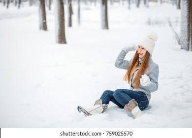 Outdoor close-up portrait of young beautiful happy smiling girl holding snow in hands. Dressed in winter clothes and a white hat. Sitting in the snow and playing snowballs.