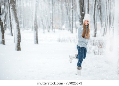 Outdoor close-up portrait of young beautiful happy smiling girl holding snow in hands. Dressed in winter clothes and a white hat, standing in the winter forest.