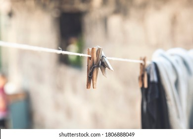 Outdoor clothesline with hanging clothespins. Concept of housework, chores, laundry and energy cost savings.