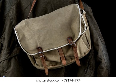 Outdoor coat and old game bag on a black background