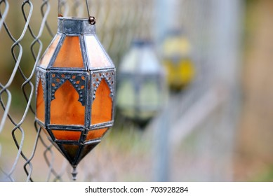 Outdoor colored glass votive lanterns hanging on chain link fence. Orange, green , and yellow lanterns.