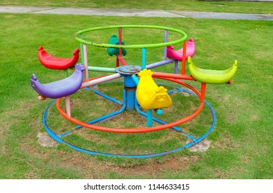 Outdoor colorful carrousel on green grass, children playground in village park, merry-go-round