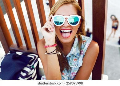 Outdoor colorful summer closeup of young pretty blonde happy smiling girl showing tongue and having fun on the street