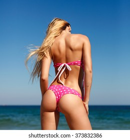 Outdoor colorful sunny portrait of sexy back of beautiful longhaired blonde woman posing on the beach near blue sea and sky background