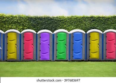 outdoor colourful portaloos in a line