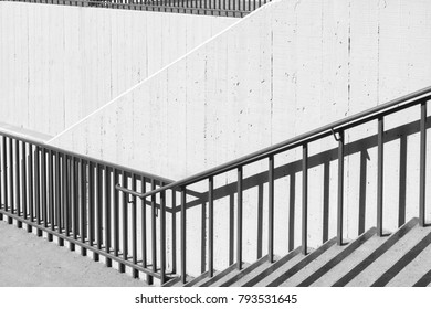 Outdoor concrete stairs. Hard shadow of metal railing on textured walls. Diagonal, zig zag composition. Black and white photo.