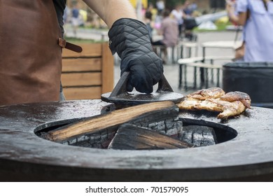 Outdoor cooking. The man cooks in a protective glove cooks on a flat surface of a grilled chicken tabaka, pressing meat of metal weight