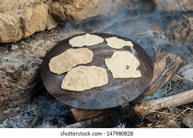 Outdoor Cooking preparing a flat bread Pita on a Saj