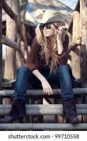 An outdoor country style fashion portrait of a beautiful long-haired blond young woman wearing a cowboy hat and sunglasses. Shallow depth of field.