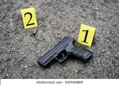 outdoor crime scene investigation. black pistol and marks