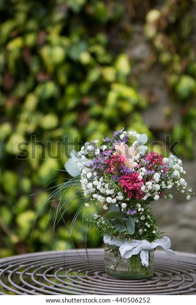 Outdoor decorative flower arrangement with gypsophila and rose flowers. in a glass jar. Wedding decor.