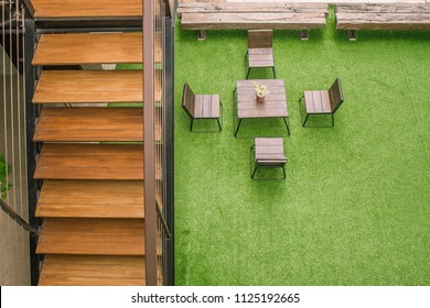 Outdoor Design Concept. Top view of wooden staircase with chairs and desk on green artificial grass in vintage style. (Selective focus)
