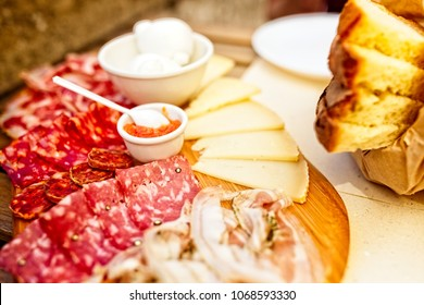 Outdoor dining in Matera, Italy in 2017. Food including cured meats, salami, prosciutto, ham, hard cheese, mozzarella balls, fresh bread and a tomato and olive tapenade
