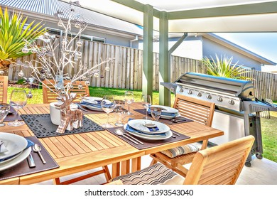 Outdoor dining table with ceramic and decorations, glasses also knifes near plates,  christmas accesories with trees, oven near the wooden chair.