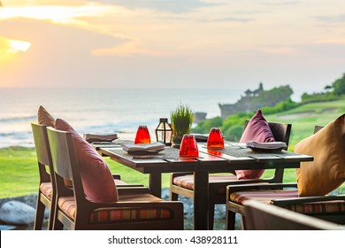 Outdoor dinner setting at sunset overlooking the coastline of a beautiful tropical Island.