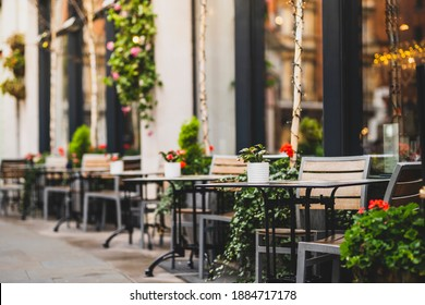 Outdoor empty coffee and restaurant terrace with potted plants tables and chairs in london indie and hipster style - Shutterstock ID 1884717178