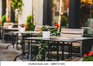 Outdoor empty coffee and restaurant terrace with potted plants tables and chairs in london indie and hipster style