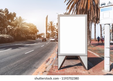 Outdoor empty informational board placeholder; white blank city billboard mock-up near the road; vertical blank advertising banner template on the sidewalk between the embankment and the highway