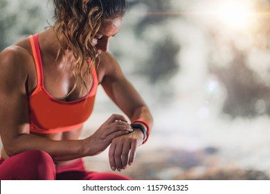 Outdoor exercising. Female athlete using fitness band to track her activities