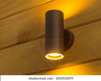 Outdoor exterior small cylinder lamp on wooden wall. External illumination