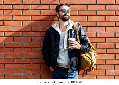 Outdoor fall or winter portrait of handsome hipster man with beard in hat , grey hoodie and leather jacket with bag pack holding cup of hot coffee. Brick urban wall background.