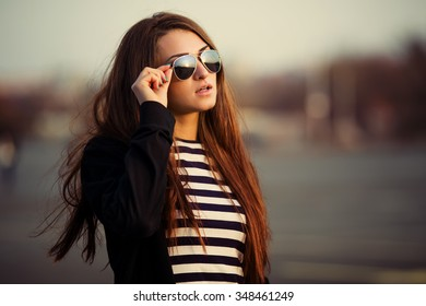 Outdoor fashion closeup portrait of nice pretty young hipster woman posing in sunglasses at sunset walks along the streets of the city.