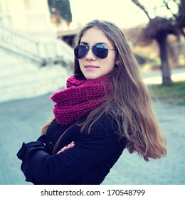 Outdoor fashion closeup portrait of young pretty woman on street