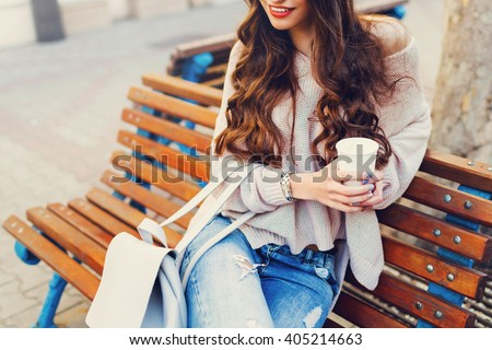 Outdoor fashion details. Sunny lifestyle  image of   stylish young  attractive woman in cozy knitted sweater  , holding cup of  hot  beverage , sitting on wooden  city bench.