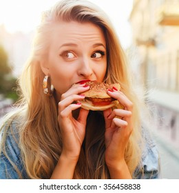 Outdoor fashion funny hipster style portrait of beautiful blonde woman eating tasty hamburger on the street