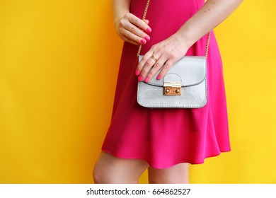 Outdoor fashion girl in pink dress in hand little bag clutch near yellow wall . Beauty accessory