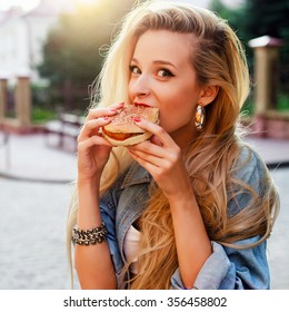 Outdoor fashion hipster style portrait of beautiful blonde woman eating tasty hamburger on the street having fun