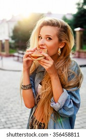 Outdoor fashion hipster style portrait of beautiful blonde woman eating tasty hamburger on the street smiling having fun