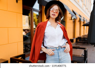 Outdoor fashion image of graceful girl in white blouse, orange jacket and trendy glasses. Happy woman walking on street. Modern cafe with yellow walls on background.