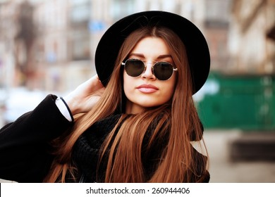 Outdoor fashion image of stylish beautiful brunette young woman wearing scarf, sunglasses and vintage hat, walking on the street.