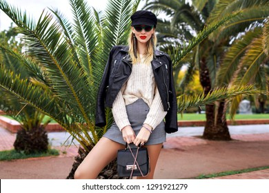 Outdoor fashion image of stylish elegant woman posing at Barcelona streets near palm trees, wearing leather jacket, cap, retro sunglasses, small bag, white cozy sweater and trendy jewelry, mini skirt.
