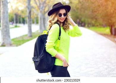 Outdoor fashion image of stylish hipster girl wearing neon sweater sunglasses and vintage hat, walking with back pack on the street in nice sunny fall autumn day.