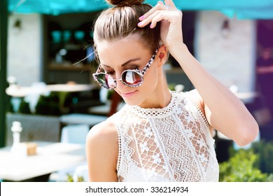 Outdoor fashion image of stylish young lady,fashionable.Lifestyle portrait of stunning hipster girl, wearing elegant glamour jacket dress and vintage sunglasses, toned warm colors, positive mood