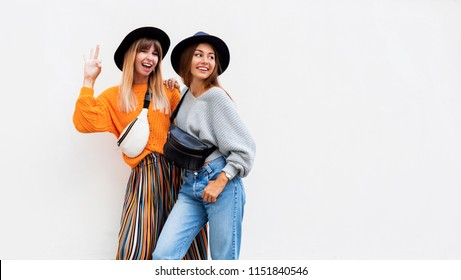 Outdoor fashion image of two models in stylish casual outfit , black hat, bum bag and trendy cardigan.Space for text.