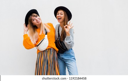 Outdoor fashion image of two models  in stylish orange sweater and multicolor stripe culotte, oversize orange knitted sweater, trendy bum bag and hat.Space for text. Brunette girl showing ok sign.