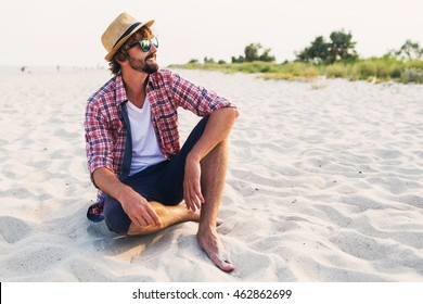 Outdoor fashion lifestyle image  with beard   of young traveler handsome hipster man sitting on white sand, beautiful beach, enjoying amazing  view sunset. Wearing  straw  hat, sunglasses.