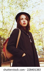 Outdoor fashion lifestyle urban portrait of young hipster woman traveling with backpack. Wearing black coat and hat. Photo toned style Instagram filters.