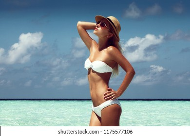 Outdoor fashion photo of beautiful happy woman at sea. Beach travel. Summer vibes.
