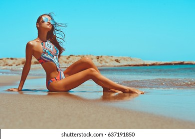 Outdoor fashion photo of beautiful happy slender woman sitting at sea. Beach travel. Summer vibes