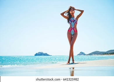 Outdoor fashion photo of beautiful happy slender woman at sea. Beach travel. Summer vibes
