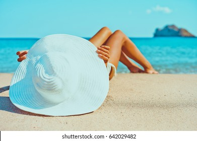 Outdoor fashion photo of beautiful happy woman lying at sea. Beach travel. Summer vibes
