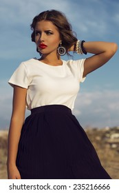 Outdoor fashion photo of the beautiful Italian woman brunette with curly hair in a white blouse and black skirt with bright makeup on a sky background