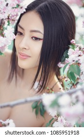 Outdoor fashion photo of beautiful young asian woman surrounded by flowers on spring. Perfect model with creative vivid makeup and pink lipstick on lips and traditional japanese hairstyle smiling and