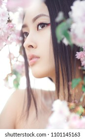 Outdoor fashion photo of beautiful young asian woman surrounded by flowers on spring. Perfect model with creative vivid makeup and pink lipstick on lips and traditional japanese hairstyle posing