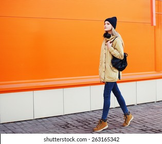 Outdoor fashion photo of stylish hipster cool girl walking in the city against a colorful urban wall