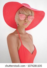 Outdoor fashion photo of young beautiful lady in red hat and sunglasses. Summer Beach travel. Summer vibes